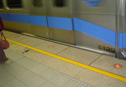 At the MRT station: As the train approaches, the red lights on the floor begin to flash!